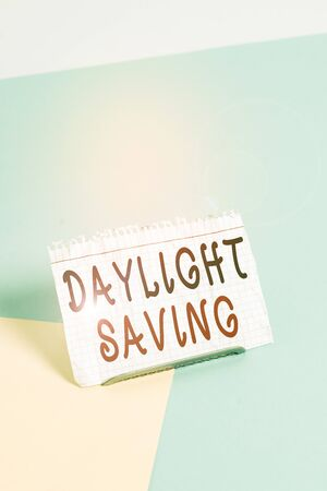 Text sign showing Daylight Saving. Business photo text turning the clock ahead as warmer weather approaches Paper placed tilted above buffer wire on soft pastel multi colours backdrop Stock Photo