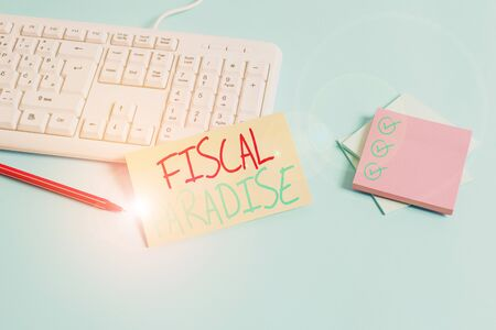 Conceptual hand writing showing Fiscal Paradise. Concept meaning Tax on development Rates of taxation for foreign investors Paper blue keyboard office study notebook chart numbers memo