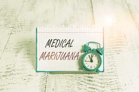 Word writing text Medical Marijuana. Business photo showcasing recommended by examining as treatment of a medical condition Mini blue alarm clock stand tilted above buffer wire in front of notepaper