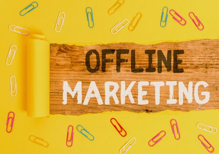 Word writing text Offline Marketing. Business photo showcasing Advertising strategy published outside of the internet Paper clip and torn cardboard placed above a wooden classic table backdrop 스톡 콘텐츠