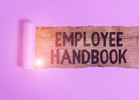 Handwriting text Employee Handbook. Conceptual photo states the rules and regulations and policies of a company Cardboard which is torn in the middle placed above a wooden classic table 写真素材