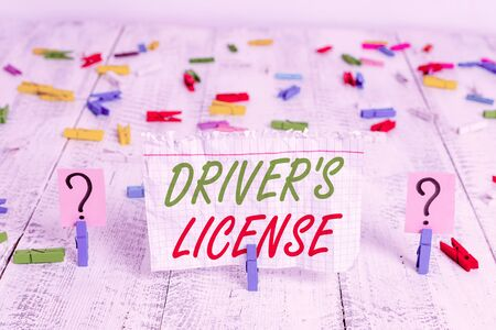 Writing note showing Driver S License. Business concept for a document permitting a demonstrating to drive a motor vehicle Crumbling sheet with paper clips placed on the wooden table Imagens