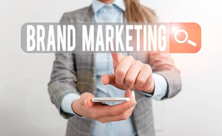Writing note showing Brand Marketing. Business concept for creating a name that identifies and differentiates a product Business concept with mobile phone and business woman Banco de Imagens