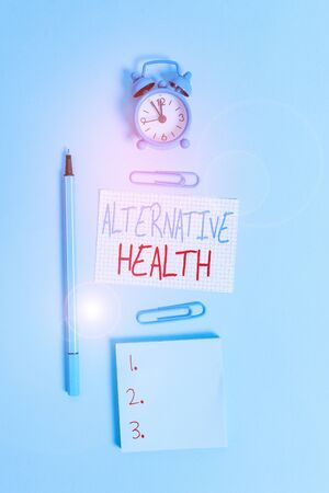 Conceptual hand writing showing Alternative Health. Concept meaning products and practices that are not part of standard care Alarm clock squared paper notepad marker clips colored background