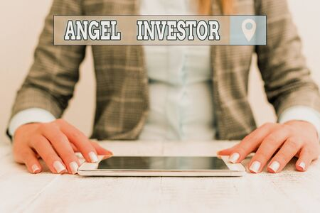 Text sign showing Angel Investor. Business photo showcasing high net worth individual who provides financial backing Business woman sitting with mobile phone on the table Stock Photo - 139826634