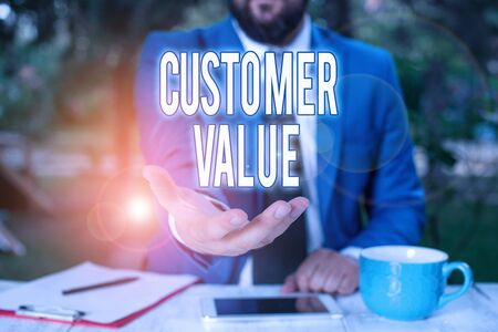 Word writing text Customer Value. Business photo showcasing level of satisfaction of your customer towards your business Man with opened hands in fron of the table. Mobile phone and notes on the table