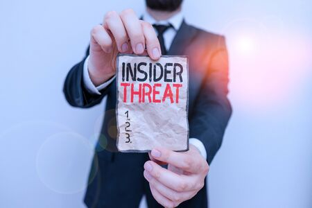 Text sign showing Insider Threat. Business photo showcasing security threat that originates from within the organization Male human wear formal work suit office look hold notepaper sheet use hand