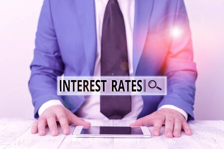 Text sign showing Interest Rates. Business photo showcasing proportion of a loan charged as interest to the borrower Businessman in blue suite with a tie holds lap top in hands