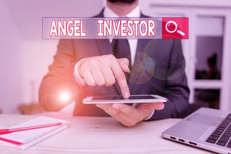 Handwriting text Angel Investor. Conceptual photo high net worth individual who provides financial backing Male human wear formal clothes present presentation use hi tech smartphone Stock Photo