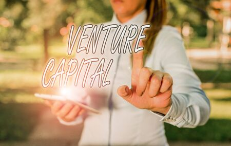 Text sign showing Venture Capital. Business photo text capital invested in a project in which there is risk Woman in a blue business shirts pointing with her finger into empty space