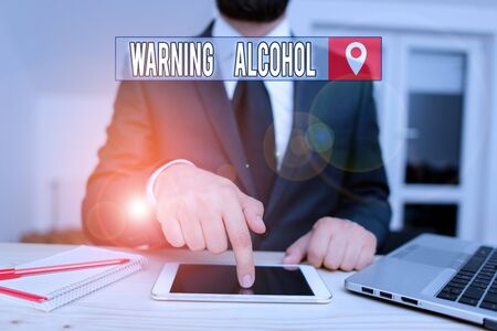 Conceptual hand writing showing Warning Alcohol. Concept meaning messages appear on the packaging of alcoholic beverages Male human wear formal clothes present use hitech smartphone