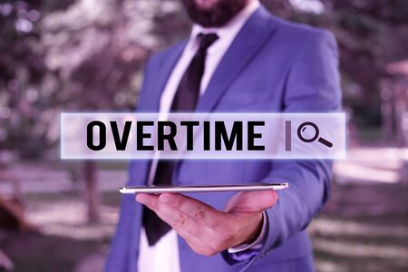 Word writing text Overtime. Business photo showcasing Time or hours worked in addition to regular working hours Businessman in blue suite stands with mobile phone in hands