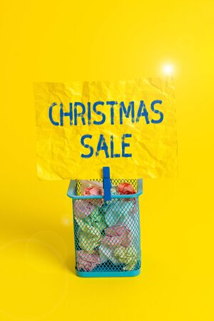 Text sign showing Christmas Sale. Business photo text period during which a retailer sells goods at reduced prices Trash bin crumpled paper clothespin empty reminder office supplies yellow