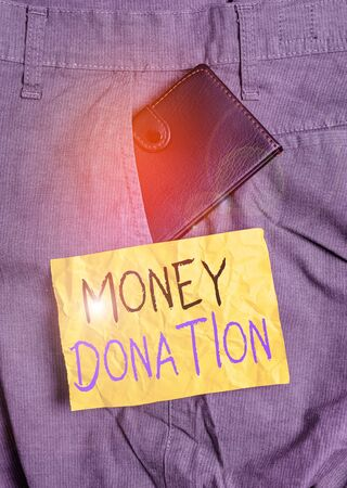 Word writing text Money Donation. Business photo showcasing something which someone gives to a charity or other Small little wallet inside man trousers front pocket near notation paper