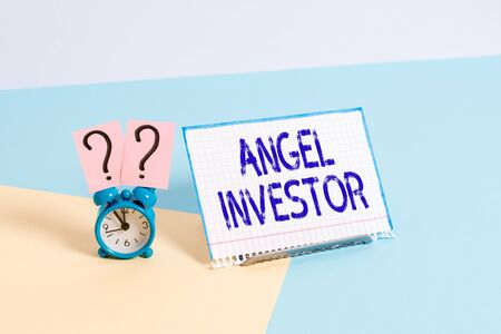 Text sign showing Angel Investor. Business photo showcasing high net worth individual who provides financial backing Mini size alarm clock beside a Paper sheet placed tilted on pastel backdrop
