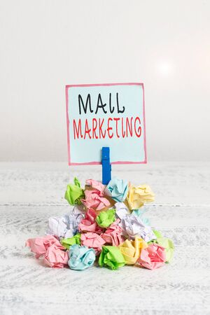 Word writing text Mail Marketing. Business photo showcasing act of sending a commercial message to a group of showing Reminder pile colored crumpled paper clothespin reminder white wooden space