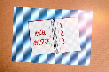 Conceptual hand writing showing Angel Investor. Concept meaning high net worth individual who provides financial backing Striped paperboard cardboard office study supplies chart