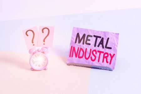 Handwriting text Metal Industry. Conceptual photo primarily concerned with metallurgy and metalworking Mini size alarm clock beside a Paper sheet placed tilted on pastel backdrop Zdjęcie Seryjne