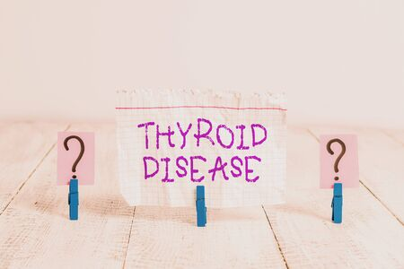 Conceptual hand writing showing Thyroid Disease. Concept meaning the thyroid gland fails to produce enough hormones Crumbling sheet with paper clips placed on the wooden table