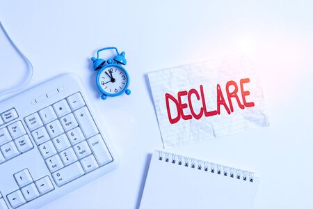 Conceptual hand writing showing Declare. Concept meaning make known or state clearly especially in explicit or formal terms Paper with copy space on table with clock and keyboard Stock Photo