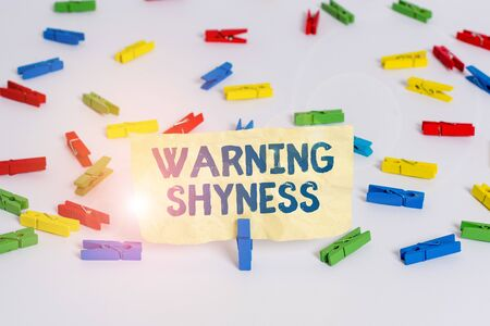 Handwriting text writing Warning Shyness. Conceptual photo Lack of confidence Not able to speak out or express oneself Colored clothespin papers empty reminder white floor background office