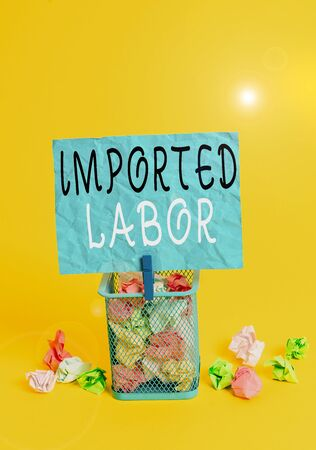 Writing note showing Imported Labor. Business concept for human who works in a country which he or she is not a citizen Trash bin crumpled paper clothespin office supplies yellow