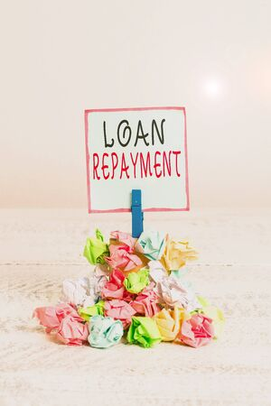 Word writing text Loan Repayment. Business photo showcasing act of paying back money previously borrowed from a lender Reminder pile colored crumpled paper clothespin reminder white wooden space