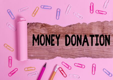 Text sign showing Money Donation. Business photo showcasing something which someone gives to a charity or other Stationary and torn cardboard placed above a wooden classic table backdrop