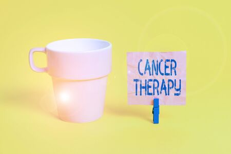 Text sign showing Cancer Therapy. Business photo showcasing treatment of cancer in a patient often with surgery Cup empty paper blue clothespin rectangle shaped reminder yellow office