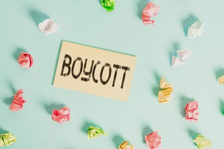 Word writing text Boycott. Business photo showcasing stop buying or using the goods or services of a certain company Colored crumpled rectangle shaped reminder paper light blue background