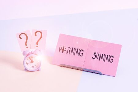 Word writing text Warning Sinning. Business photo showcasing stop the action which is believed to break the laws Mini size alarm clock beside a Paper sheet placed tilted on pastel backdrop
