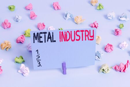 Writing note showing Metal Industry. Business concept for primarily concerned with metallurgy and metalworking Colored crumpled papers empty reminder blue floor background clothespin