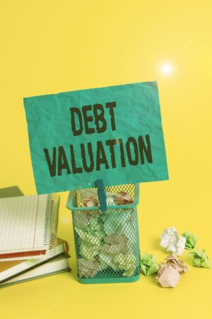 Text sign showing Debt Valuation. Business photo showcasing process of determining the current worth of an asset Trash bin crumpled paper clothespin empty reminder office supplies yellow