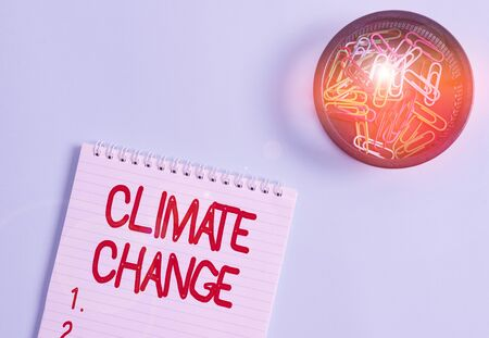 Conceptual hand writing showing Climate Change. Concept meaning change in the expected pattern of average weather of a region Blank notebook and stationary placed above pastel colour backdrop Stock Photo