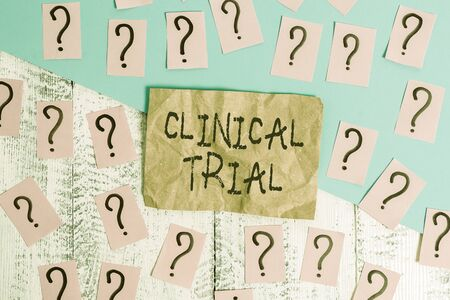 Word writing text Clinical Trial. Business photo showcasing trials to evaluate the effectiveness and safety of medication Scribbled and crumbling papers with thick cardboard above wooden table