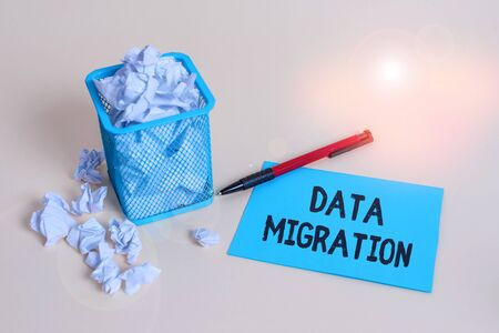 Word writing text Data Migration. Business photo showcasing process of transferring data between data storage systems crumpled paper trash and stationary with note paper placed in the trash can