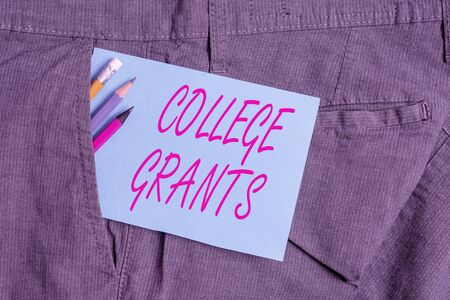 Handwriting text College Grants. Conceptual photo monetary gifts to showing who are pursuing higher education Writing equipment and blue note paper inside pocket of man work trousers Stock Photo