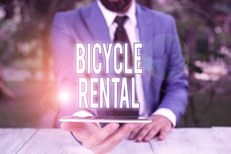 Conceptual hand writing showing Bicycle Rental. Concept meaning a business which rents out bikes to tourists or travellers Businessman with mobile phone in his hand
