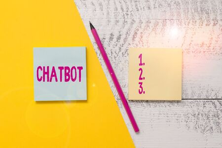 Conceptual hand writing showing Chatbot. Concept meaning a kind of computer program that simulates human conversation Blank notepads pen colored paper sheet wooden background