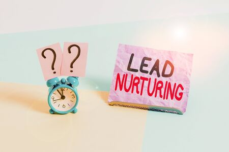 Handwriting text Lead Nurturing. Conceptual photo method of building a relationship with potential customers Mini size alarm clock beside a Paper sheet placed tilted on pastel backdrop