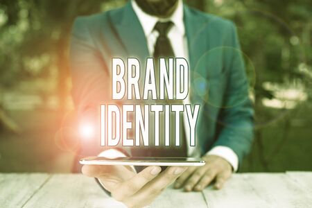 Conceptual hand writing showing Brand Identity. Concept meaning visible elements of a brand that identify and distinguish Businessman with mobile phone in his hand Foto de archivo