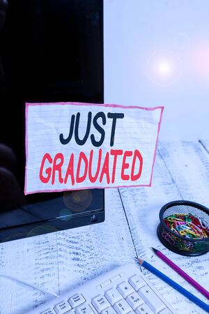 Handwriting text writing Just Graduated. Conceptual photo demonstrating who has finished their school or university education Note paper taped to black computer screen near keyboard and stationary