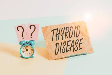 Word writing text Thyroid Disease. Business photo showcasing the thyroid gland fails to produce enough hormones Mini size alarm clock beside a Paper sheet placed tilted on pastel backdrop