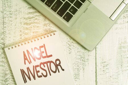 Writing note showing Angel Investor. Business concept for high net worth individual who provides financial backing Top trendy metallic laptop blank spiral notepad lying on wooden table Stock Photo