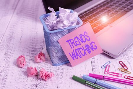 Word writing text Trends Watching. Business photo showcasing change or development towards something new or different Laptop sticky note waste basket crushed paper ball clips pens vintage table