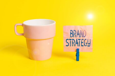 Text sign showing Brand Strategy. Business photo showcasing Longterm plan for the development of a successful brand Cup empty paper blue clothespin rectangle shaped reminder yellow office