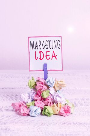Word writing text Marketing Idea. Business photo showcasing activities that seek to gain market share for a concept Reminder pile colored crumpled paper clothespin reminder white wooden space Banque d'images