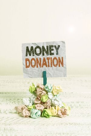 Writing note showing Money Donation. Business concept for something which someone gives to a charity or other Reminder pile colored crumpled paper clothespin wooden space Imagens