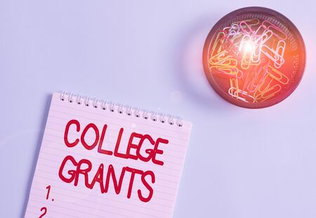 Conceptual hand writing showing College Grants. Concept meaning monetary gifts to showing who are pursuing higher education Blank notebook and stationary placed above pastel colour backdrop Stock Photo