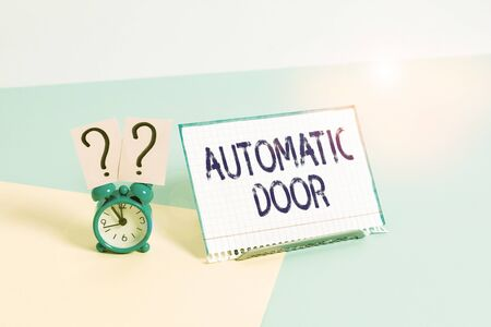 Text sign showing Automatic Door. Business photo showcasing opens automatically when sensing the approach of person Mini size alarm clock beside a Paper sheet placed tilted on pastel backdrop